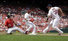 Washington Nationals' Nate McLouth, left, is safe at first as he beats St. Louis Cardinals first baseman Matt Adams, right, to the bag and Cardinals' Jaime Garcia watches during the fifth inning of a baseball game on Sunday, June 15, 2014, in St. Louis. (AP Photo/Jeff Roberson)