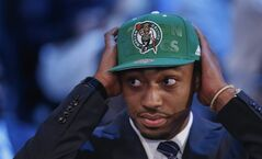 Kentucky's James Young dons a Boston Celtics cap after being selected as the 17th overall pick by the Celtics during the 2014 NBA draft, Thursday, June 26, 2014, in New York. (AP Photo/Kathy Willens)