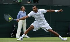 Jo-Wilfried Tsonga of France stretches to reach the ball as he returns to Juergen Melzer of Austria during their first round match at the All England Lawn Tennis Championships in Wimbledon, London, Monday, June 23, 2014. (AP Photo/Ben Curtis)