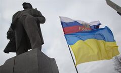 The Russian and Ukrainian flags fly, next to the statue of Vladimir Ilyich Lenin, in Donetsk, eastern Ukraine, Tuesday, Feb. 25, 2014. The Ukrainian parliament on Tuesday delayed the formation of a new government, reflecting political tensions and economic challenges following the ouster of the Russia-backed president. Parliament speaker Oleksandr Turchinov, who was named Ukraine's interim leader after President Viktor Yanukovych fled the capital, said that a new government should be in place by Thursday, instead of Tuesday, as he had earlier indicated. (AP Photo/Darko Bandic)