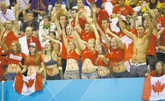 Supporters of Canada's Ryan Cochrane cheer as he swims in the men's 1,500-metre freestyle final at the Aquatics Centre in the Olympic Park on Saturday.
