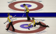 Manitoba skip Jennifer Jones (right) makes a shot as second Jill Officer and lead Dawn Askin look on during a draw against P.E.I. at the Scotties Tournament of Hearts in Red Deer, Alta., on Sunday.