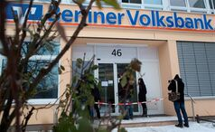 Customers and a cameraman stand in front of a bank in Berlin Monday. German police say a 30-metre tunnel dug by robbers who raided the Berliner Volksbank was