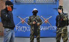 Pro Russian militants stand in front of a gate with graffiti reading