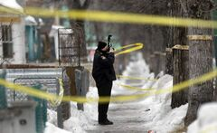 A Winnipeg police forensics officer photographs part of the 500 block of Langside Street Wednesday morning after a fatal shooting there Tuesday.