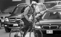 A Winnipeg cyclist navigates traffic on April 24.