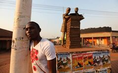 Oundo, our team's guide, at a monument in Gulu that features a boy and girl with an open book. It symbolizes how children can freely and peacefully go to school, he explains.