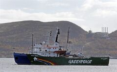FILE - In this Tuesday, Sept. 24, 2013 file photo, Greenpeace ship 'Arctic Sunrise' is escorted by a Russian coast guard boat, in Kola Bay at the military base Severomorsk on the Kola peninsula in Russia, at dawn. Greenpeace has suffered a 3.8 million-euro ($5.2 million) loss on an ill-timed bet in the currency market by a well-intentioned — if reckless — employee in its financial unit. The environmental group, which is based in Amsterdam, said Monday, June 16, 2014, the employee — who had bet the euro would not strengthen against other currencies in 2013, when it did — had acted beyond the limits of his authority. (AP Photo/Efrem Lukatsky, File)