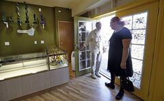 Carl Ettner, left, and Avalon Zanoni walk out of Cannabis City empty-handed after learning that the new marijuana shop was still days from opening Wednesday, July 2, 2014, in Seattle. The empty display cases are expected to be filled with pot for sale beginning Tuesday, July 8, the first day that recreational marijuana can legally be sold in Washington state and the store is expected to be the first licensed retailer in Seattle. (AP Photo/Elaine Thompson)