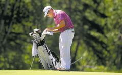 Leader Erik Barnes focuses on cleaning his ball prior to putting on the 11th green at Pine Ridge on Friday afternoon.
