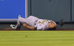Oakland Athletics center fielder Coco Crisp falls on his back after trying to catch a two-run home run by Los Angeles Angels' Chris Iannetta during the fifth inning of a baseball game, Friday, Aug. 29, 2014, in Anaheim, Calif. Crisp was taken out of the game after the play. (AP Photo/Mark J. Terrill)