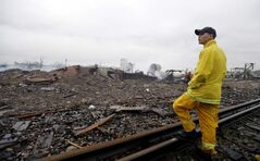 A firefighter stands on a rail line and surveys the remains of a fertilizer plant destroyed by an explosion in West, Texas, Thursday.