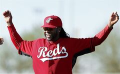 Cincinnati Reds pitcher Johnny Cueto smiles while stretching during spring training baseball practice in Goodyear, Ariz., Saturday, Feb. 15, 2014. (AP Photo/Paul Sancya)