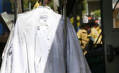 A rack of chef's jackets stands outside the fire-damaged Manresa restaurant in Los Gatos, Calif., Monday, July 7, 2014. The top-rated Northern California restaurant was severely damaged and a firefighter is recovering from injuries after an early morning fire. (AP Photo/Bay Area News Group, Karl Mondon)