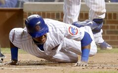 Chicago Cubs' Starlin Castro grimaces after injuring himself while sliding safely into home plate, scoring on a single by Jorge Soler, during the first inning of a baseball game against the Milwaukee Brewers, Tuesday, Sept. 2, 2014, in Chicago. (AP Photo/Charles Rex Arbogast)