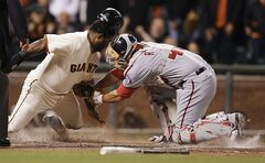 Washington Nationals catcher Wilson Ramos, right, tags out San Francisco Giants' Pablo Sandoval in the sixth inning of a baseball game Tuesday, June 10, 2014, in San Francisco. Sandoval was attempting to score on a hit by Giants' Brandon Crawford. (AP Photo/Ben Margot)