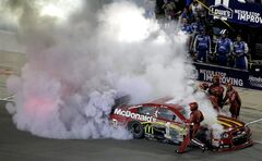 Jamie McMurray is helped from his car during a NASCAR Sprint Cup Series auto race at Kansas Speedway in Kansas City, Kan., Saturday, May 10, 2014. (AP Photo/Charlie Riedel)