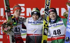 Winner Kamil Stoch of Poland, center, is flanked by second placed Peter Prevc of Slovenia, left, and third placed Anders Jacobsen of Norway on the podium after winning the men's ski jumping final of the Nordic Ski World Championships in Val di Fiemme, Italy, Thursday, Feb. 28, 2013. (AP Photo/Matthias Schrader)