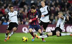 FC Barcelona's Lionel Messi, second left, duels the ball against Valencia's Juan Bernat, left, and Oriol Romeu, right, during a Spanish La Liga soccer match at the Camp Nou stadium in Barcelona, Spain, Saturday, Feb. 1, 2014. (AP Photo/Manu Fernandez)