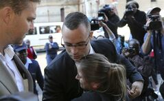 Oscar Pistorius, center top, receives a hug from his fan Kayla Nolan as he arrives at the high court in Pretoria, South Africa, Monday, May 5, 2014. Pistorius' murder trial enters a critical phase Monday as his defense team attempts to recover from a faltering start and reinforce the disabled athlete's claim that he fatally shot girlfriend Reeva Steenkamp by mistake because he was overwhelmed by a long-held fear of violent crime. (AP Photo/Themba Hadebe)