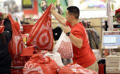 In this Nov. 23, 2012 photo, a Target employee hands bags to a customer at the register at a Target store in Colma, Calif. THE CANADIAN PRESS/AP, Jeff Chiu