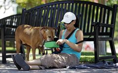 In this photo taken Friday, June 28, 2013, Monee Hauducoeur, from Upland, Calif., keeps a bowl of fresh water for her dog,