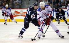 Winnipeg Jets' Bryan Little dogs New York Rangers' Derek Stepan in second-period action Wednesday at the's MTS Centre.