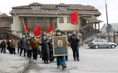 Georgians carry a portrait of former Soviet dictator Joseph Stalin and red flags during a ceremony marking the 60th anniversary of Stalin's death in his home town of Gori, some 80 km (50 miles) west of the Georgian capital Tbilisi, Tuesday, March 5, 2013. Georgian communists, who flocked to Stalin's hometown of Gori for the anniversary on Tuesday, hope that the government of Prime Minister Bidzina Ivanishvili, whose bloc defeated Saakashvili's party in parliamentary elections last fall, will restore the Stalin monument torn down on Georgian President Mikhail Saakashvili's orders. (AP Photo/Shakh Aivazov)