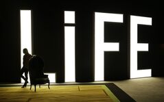 In this photo taken on Aug. 20, 2014, a woman stands in front of a sign for Life Nightclub in the SLS Las Vegas in Las Vegas. The hotel and casino, formally known as the Sahara, has gone through extensive renovations is scheduled to open this weekend. (AP Photo/John Locher)