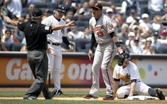 Baltimore Orioles third baseman Manny Machado (13) argues with third base umpire Tom Hallion who ruled New York Yankees' Brett Gardner safe at third on a first-inning triple in a baseball game at Yankee Stadium in New York, Sunday, June 22, 2014. The call was reversed after Orioles manager Buck Showalter successfully challenged the call. (AP Photo/Kathy Willens)