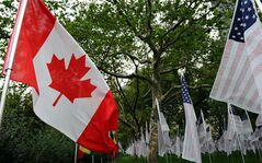A Canada flag blows in the wind alongside American flags signed with the names of 9-11 victims at Battery Park blocks from ground zero on the tenth anniversary of the terrorist attacks in New York on Sunday, September 11, 2011. THE CANADIAN PRESS/Sean Kilpatrick