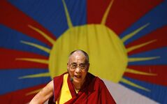 FILE - In this Nov. 27, 2012 file photo, Tibetan spiritual leader the Dalai Lama laughs as he addresses Tibetan exiles living in Bangalore, in front of the Tibetan flag, in Bangalore, India. The Dalai Lama is set to headline India's Jaipur Literature Festival to speak about faith with one of his biographers, Pico Iyer. The Tibetan spiritual leader will hold a session on the festival's first day, Thursday, Jan. 24, 2013, titled: