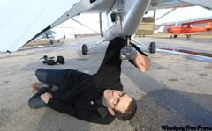 Tyler Walsh adjusts the heavily-duct taped GoPro camera mounted on the belly of a plane at Harv's Air in Steinbach.