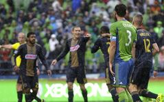 Seattle Sounders' Brad Evans (3) watches as Philadelphia Union players celebrate after Evans was charged with an own goal in the first half of an MLS soccer match on Saturday, May 3, 2014, in Seattle. (AP Photo/Ted S. Warren)