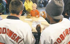 Will Sagel gets a signed ball from Goldeyes David Narodowski (left) and Chris Roberson during a player/fan get-together at Shaw Park on Monday.