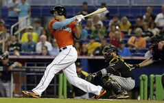 Miami Marlins' Giancarlo Stanton, left, follows through on a base hit against the Pittsburgh Pirates in the first inning of a baseball game in Miami, Sunday, June 15, 2014. (AP Photo/Alan Diaz)