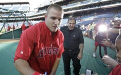Los Angeles Angels' Mike Trout signs autographs before the start of a baseball game with the Philadelphia Phillies, Tuesday, May 13, 2014, in Philadelphia. (AP Photo/Laurence Kesterson)
