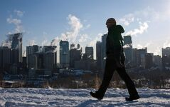 A man walks past a the Calgary, Alta., skyline during a deep freeze on Jan. 31, 2011. The kind of winter you're in for depends entirely on which side of the country you live in. Western Canada should hunker down for a colder than normal winter. THE CANADIAN PRESS/Jeff McIntosh