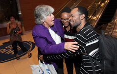 Phyllis Reader embraces Quesney Ramazani-Buledi and his son, Didier, as they arrive in Winnipeg Wednesday evening.