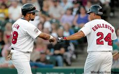 Goldeyes' Luis Alen (left) gets congrats from Aharon Eggleston after scoring a run against the T-Bones in the bottom of the fifth Friday night.