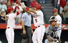 Los Angeles Angels' Collin Cowgill, left, celebrates at home plate with designated hitter Albert Pujols (5) after Pujols' two-run home run in the fourth inning of a baseball game as Houston Astros catcher Carlos Corporan, right, looks away on Friday, July 4, 2014, in Anaheim, Calif. (AP Photo/Alex Gallardo)