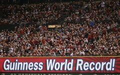 As part of a Christmas in June promotion fans try to set a Guinness World Record for the most people wearing santa hat during the fifth inning of a baseball game between the Los Angeles Angels and the Minnesota Twins in Anaheim, Calif., Wednesday, June 25, 2014. (AP Photo/Chris Carlson)