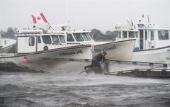A lobster fisherman slips but holds on while trying to secure lines to his fishing boat after the floating dock broke apart during Tropical storm Arthur in Escuminac, N.B. on Saturday, July 5, 2014. THE CANADIAN PRESS/Diane Doiron