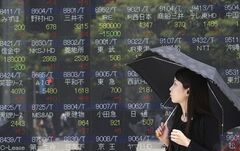 A woman looks at an electronic stock board of a securities firm in Tokyo, Monday, June 2, 2014. Share prices rose cautiously in Asia on Monday, after the Dow Jones index closed last week at a record high and market players waited for a U.S. jobs report later in the week for confirmation of such optimism about the American economy. The Nikkei, the benchmark for the Tokyo Stock Exchange, was trading at 14,827.39, gaining 1.3 percent in the first hour of trading. (AP Photo/Koji Sasahara)
