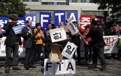 South Korean farmers smash boxes symbolizing the Free Trade Agreement between South Korea, Japan, and China during a rally denouncing the FTA talks in front of the venue where the discussions are being held, in Seoul, South Korea, Tuesday, March 26, 2013. Negotiations for a Free Trade Agreement between the three countries will be held from March 26 - 28. The writing reads