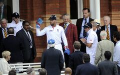 England's Matt Prior, centre with cap, and Andrew Strauss, right with cap apologize to MCC members underneath a broken window during the 5th day of the second test match at Lord's cricket ground, London, Tuesday.