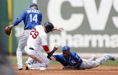 Kansas City Royals' Alcides Escobar, right, holds up the ball next to Omar Infante (14) after getting the forced out on Boston Red Sox's Daniel Nava (29) on a fielders choice during the first inning of a baseball game in Boston, Sunday, July 20, 2014. (AP Photo/Michael Dwyer)