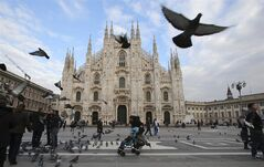 This Jan. 16, 2014 photo shows visitors dodging birds in the piazza outside of Duomo cathedral in Milan, Italy. The ornate white facade of Milan's Duomo cathedral is the single most recognized symbol of the Lombard capital, taking centuries to complete. (AP Photo/Antonio Calanni)