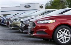 FILE - In this Wednesday, May 8, 2013 file photo, a row of new 2013 Ford Fusions are on display at an automobile dealership in Zelienople, Pa. As the auto industry strives to sustain its post-recession comeback, car companies are resorting to tactics that some experts warn will lead to trouble down the road. (AP Photo/Keith Srakocic, File)