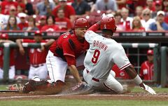 Philadelphia Phillies' Domonic Brown, right, is tagged out at home plate by Cincinnati Reds catcher Devin Mesoraco, left, after a Cesar Hernandez ground ball during the fourth inning of a baseball game, Sunday, June 8, 2014, in Cincinnati. (AP Photo/David Kohl)